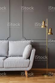 goldene stehleuchte und eine graue bequeme in ein elegantes wohnzimmer interieur mit formteil an dunklen wänden stockfoto und mehr bilder