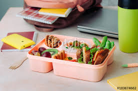 Open Lunch Box With Healthy Food On The Table Near Backpack Laptop And Thermo Mug