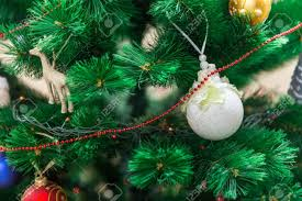 Bright White Ball Hanging On A Christmas Tree Fluffy Green With Toys And