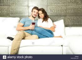 ein junges paar im wohnzimmer bei einem glas rotwein auf dem