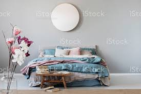 runden spiegel auf graue wand in stilvollen schlafzimmer innenraum mit warmen bett mit blau pastell rosa und beige bettwäsche und holzbank mit