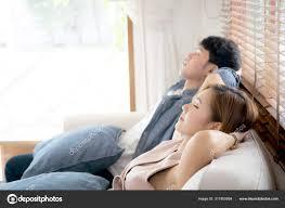 junges asiatisches paar lächelt entspannt auf sofa im