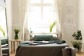 buch und decke auf dem bett in natürlichen hellen schlafzimmer innenraum mit pflanzen poster und spiegel echtes foto stockfoto und mehr bilder