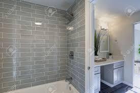 das warme und saubere badezimmer verfügt über eine duschwanne aus grauen glasfliesen und einen doppelwaschtisch mit granitplatte