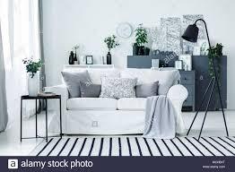grau weiß sofa mit kissen und decke im hellen wohnzimmer