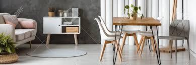offenes wohnungsdesign mit beige sofa hölzerner haarnadeltabelle und weißen stühlen im esszimmer