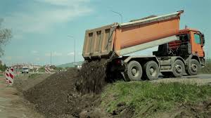 Road Works. Dump Truck Fills The Channel With Ground, Dumper Pouring ...