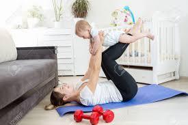 schöne junge mutter und ihr baby im wohnzimmer auf dem boden zu tun