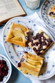 obstkuchen vom blech belegt mit schattenmorellen und apfelschnitzen