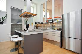 A Modern Kitchen With Frosted Glass Cabinetry And Shelving On The Side Of Room