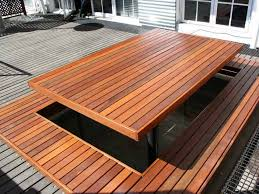 this wooden deck has a large wooden picnic table backyard