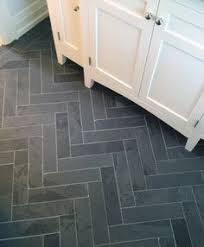 traditional mud room with herringbone tile floors built in