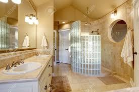 antik bad design mit glas dusche und fliesenwand hat großen spiegel an der wand und weiße schränke mit zwei waschbecken