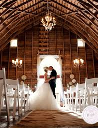 Bride And Groom Kissing In A Barn Set Up For Wedding Ceremony