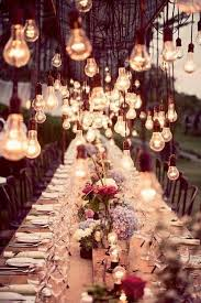 A Beautiful Dinner Table Lit By Hanging Rustic Light Bulbs For Wedding Reception