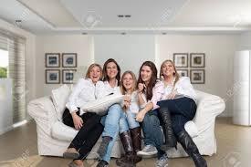 eine gruppe fünf glückliche frauen unterschiedlichen alters lachen im wohnzimmer