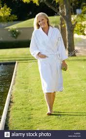 Mature Couple Wearing White Bath Robe Walking By Swimming Pool Smiling Portrait