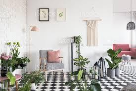 weiß gemauerte wand und rosa kissen auf einem sessel mit hahnentrittmuster im offenen raum wohnzimmer interieur mit vielen pflanzen echtes foto