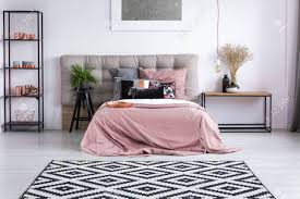 zeitgenössisches schlafzimmer mit kupferaccessoires gemusterter wolldecke und rosafarbener bettwäsche auf bequemem kingsize bett