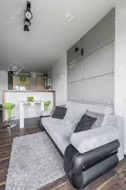 einfache und ein kleines wohnzimmer design in grau mit modernen grünen dekorationen