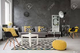geräumig grauen wohnzimmer mit sofa sessel stehle kleine kaffee tisch dekorationen in gelb schwarz und weiß