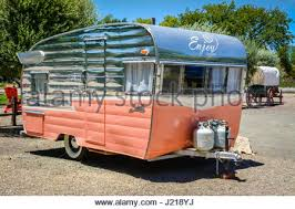 A Salmon Silver Colored Classic Charming Vintage Camper Trailer In Pristine Condition Awaits