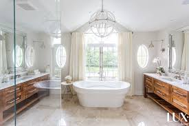 oval freestanding tub flanked by separate washstands