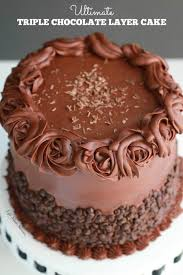 Ultimate Triple Chocolate Layer Cake A triple layer devils chocolate cake with milk chocolate frosting and partially covered with mini chocolate chips e