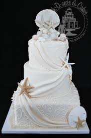 An Elegant Wedding Cake Covered With Fondant And Adorned Scrollwork Drapes