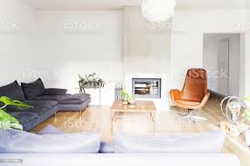 moderne und schöne wohnlandschaft mit design sofa tisch aus holz und kamin helles und sonniges wohnzimmer mit pflanzen und brauner holzboden stockfoto