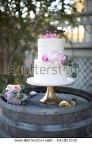 Two Tiered White Frosting Wedding Cake With Pink Flowers On Gold Stand Atop Weather Wood Wine