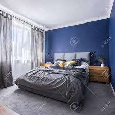 modernes kobaltblaues schlafzimmer mit doppelbett grauer bettwäsche teppichboden und fenster