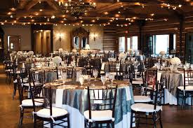 Rustic Winter Wedding Decor With Round Tables And Small Wooden Chairs Also String Lamps Plus White Flowers
