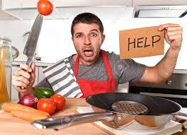 jungen erschrockenen mann zu hause küche trägt kochschutzblech das hilfe zeichen suchen verzweifelt in stress hält messer mit tomaten im inland