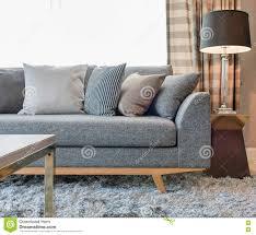 reihe kissen auf grauem sofa mit schwarzer le im