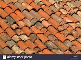 up of traditional burnt umber clay roof tiles in stock