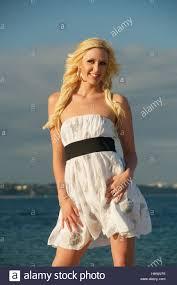 beautiful blonde in white summer dress on studland beach