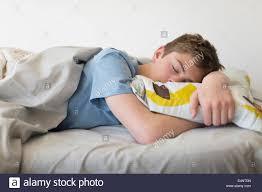 teenage boy 16 17 sleeping in bed stock photo royalty free