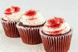 velvet cupcakes mit weißem zuckerguss und streuseln rot