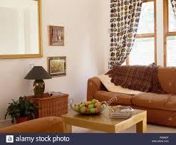 plaid werfen auf hellbraune sofa vor fenster mit obst