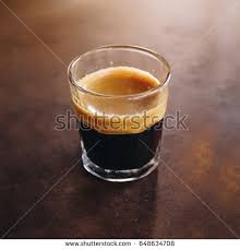 A Cup Of Espresso Shot Coffee By Barista In Glass On Rust Table Background