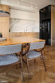 stilvolle und gemütliche skandinavische esszimmer und küche interieur mit tisch stühlen und le weißen marmorwänden und braune holzparkett stockfoto