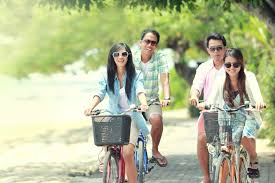 Carefree Group Friends Having Fun And Smiling Riding Bicycle During The Summer Day