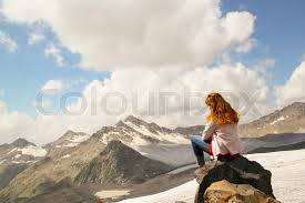 Young Girl Sitting On The Edge Of A Cliff And Looking At Sky With Clouds Mountain Peaks