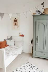 Green Painted Armoire A White Wood Bed Woven Illustrated Animal Rug And Gray Banner Garland