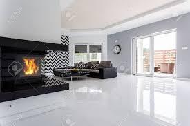 weißes und geräumiges modernes wohnzimmer mit kamin und großem sofa