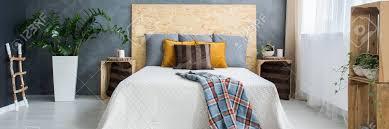 graue wand und hölzerne dekoration im gemütlichen schlafzimmer