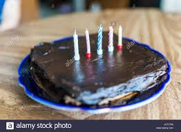 Simple square small chocolate birthday cake with five colorful candles