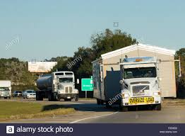 Moving home shiny American Volvo truck transporting mobile home