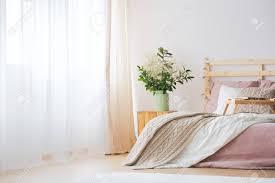 gemütliches modernes schlafzimmer mit großem fenster blumen und bett